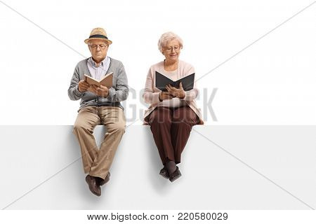 Mature man and an elderly woman sitting on a panel and reading books isolated on white background