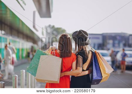 two beautiful young women walk to the shops and make purchases