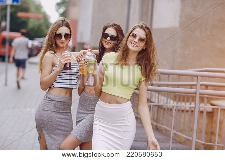 three young models are walking around the city on a warm summer day
