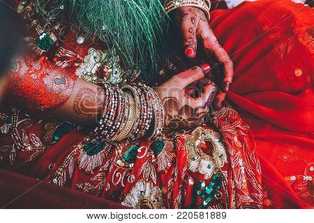 close-up partial view of woman in traditional clothes and mehendi on hands in Nepal