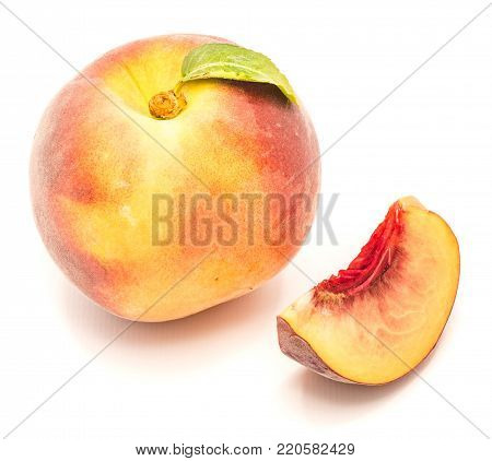 One whole peach with a green leaf and one slice isolated on white background