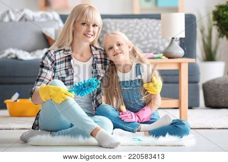Little girl and her mother with cleaning supplies at home