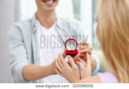 Man with engagement ring making proposal of marriage to woman at home