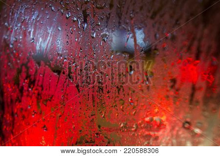 Water droplets on the glass with a blurred background and red illumination, abstract texture, background.