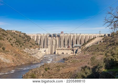 View of the retaining wall of the Alcantara dam next to the famous Roman bridge of the same name in Cáceres, Extremadura. Spain