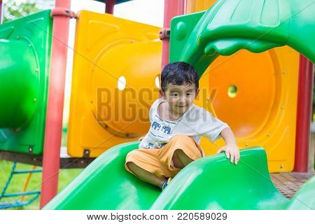 Little Asian kid playing slide at the playground under the sunlight in summer, Kids play on school yard. Happy kid in preschool. shallow DOF