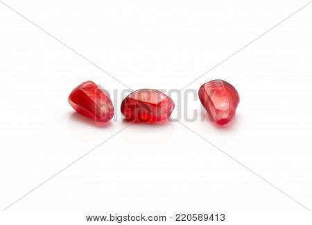 Three pomegranate grains isolated on white background poster