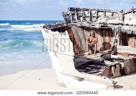 Horizontal picture. Alone sad curly-berded man is sitting on the wreck of the ship on the white sand beach. Blue ocean on the background.