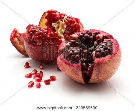 Two open pomegranate with revealed grains isolated on white background