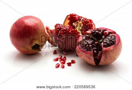 Pomegranate with revealed grains isolated on white background one whole two split open