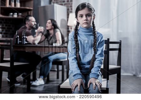 Depressive childhood. Unhappy sad young girl sitting on the chair and looking at you while living in an unhappy family