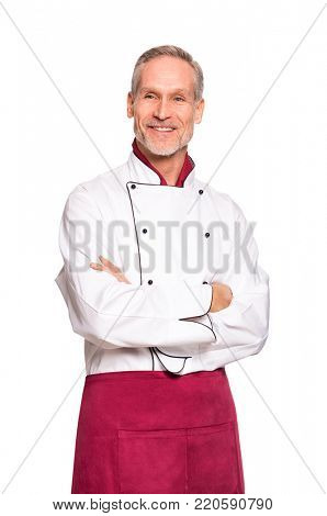 Confident professional chef with crossed hands isolated on white background. Happy mature cook with red apron and white uniform. Portrait of satisfied chef man with crossed arm looking away.
