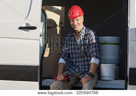 Happy mature artisan sitting in van with cardboard box and paint buckets. Smiling mature man with hardhat and work gloves ready for work. Portrait of painter sitting with box in van for moving house.