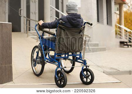 Little boy in wheelchair on ramp outdoors