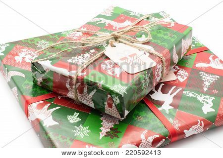 Two presents tied by red bow and decorated by Christmas illustration (tree, animals, snowflake) isolated on white background