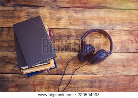 Headphones and a pile of Book on the Wooden Background. Audiobook Concept.