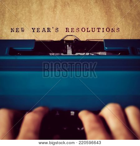 closeup of a man typewriting the text new years resolutions in a yellowish paper with a blue retro typewriter