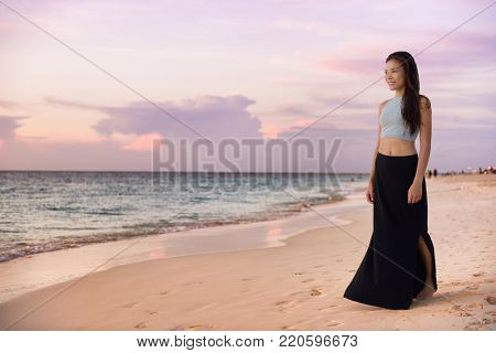 Asian model woman walking on beach at sunset relaxing on luxury Caribbean travel holiday wearing fashion maxi skirt outfit for night out on summer vacation. Chinese girl enjoying view of ocean.