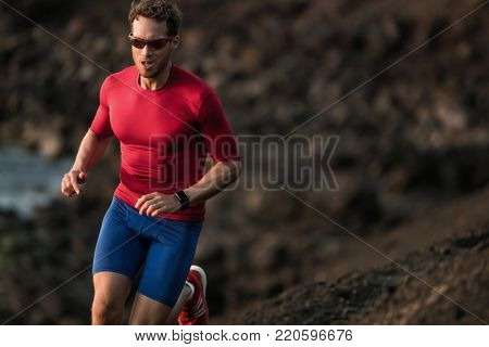 Fitness runner man sport athlete ultra running on endurance tough mud trail race competition training cardio jogging in mountain. Dark exposure of male adult in compression clothes, sunglasses.