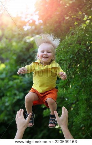 Baby boy happy falling in parent hands on idyllic summer landscape. Child, childhood, family, love, trust. Freedom, future, happiness concept.