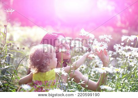 Woman And Child Smile On Sunny Floral Landscape