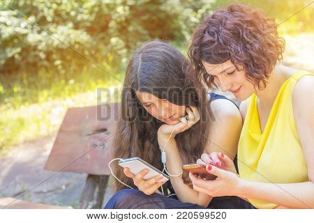 Mother and teenage daughter listening to music together in the city park on a summer sunny day. Walking in summer park on the summer day. Copy space
