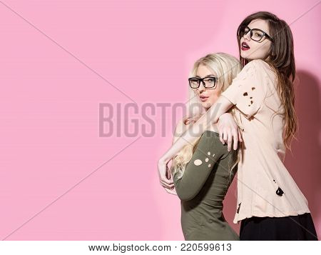 Fashion, style, vogue. Women with long hair in geek glasses. Visage, makeup, hairstyle. Girls pose in torn clothes on pink background. Beauty, look concept, copy space