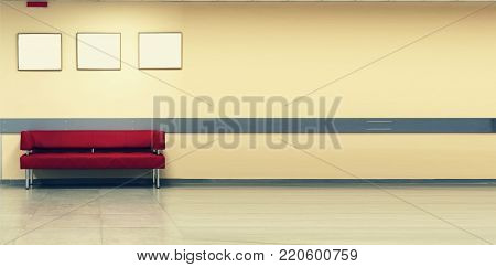 Red Sofa, interior design, office. Style minimalism. Empty waiting room with a modern red sofa in front of the door and three empty frames on the wall
