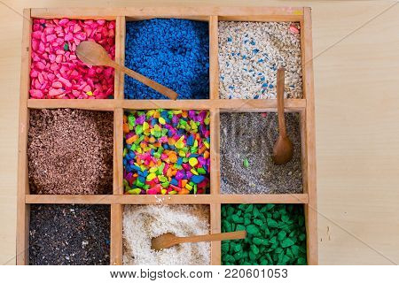 Colored pebbles mini stone and wooden spoons in wooden boxes for mini terrarium