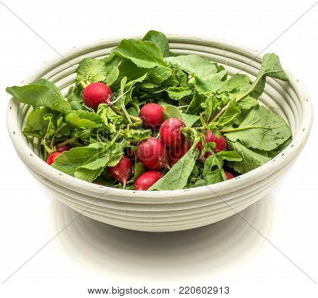 Whole red radish with fresh green leaves in rattan bowl isolated on white background