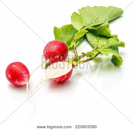 Two whole and sliced red radish, one half, fresh green leaves, isolated on white background