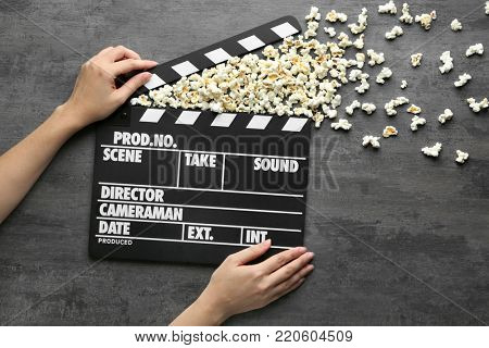 Woman holding movie clapper with popcorn shooting out of it on grey background