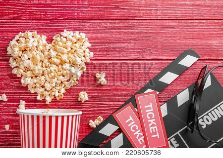 Tasty popcorn, tickets and clapboard on red wooden background, top view