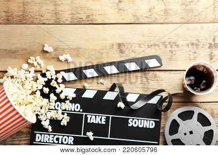 Tasty popcorn, clapboard and movie reel on wooden background