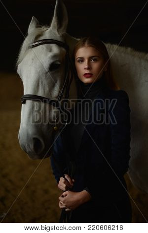 Serious blonde in blue jacket stands with a horse