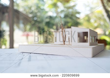 An architecture model with shop drawing paper and laptop on table in office with blur nature background
