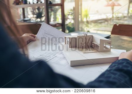 An architect working and looking at an architecture model with shop drawing paper on table