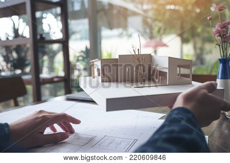An architect working and holding an architecture model with shop drawing paper on table