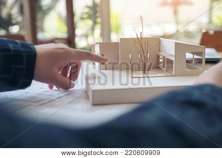 An architect working and pointing at architecture model with shop drawing paper on table