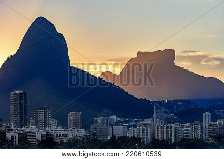 Buildings of the neighborhood of Leblon with the Two Brothers hill, Gavea stone and Rocinha slum in the background during the summer sunset