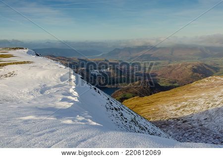 Winter scene of a snowy mountain ridge near Helvellyn in the English Lake District, with a glimpse of Thirlmere and Skiddaw on the horizon