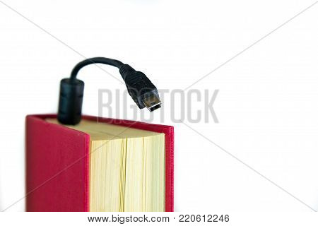 Mini USB calbe coming out of a book with red covers. Ebook concept, audio book concept or information technology. Isolated on white.