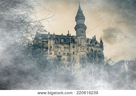 Wonderful view of the Neuschwanstein castle in the Bavaria Alps from the bridge lost in the fog with clouds