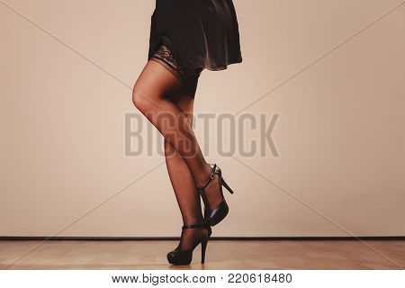 Beauty and sexuality of women. Sexy part body woman model wearing black dress skirt and pants stockings. Female legs in high heels.