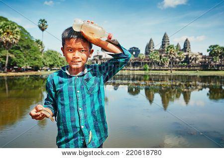 Siam Reap, Cambodia - November 10, 2017: Little boy fishing in lake in front of the famous Angkor Wat temple on November 10, 2017 in Cambodia.