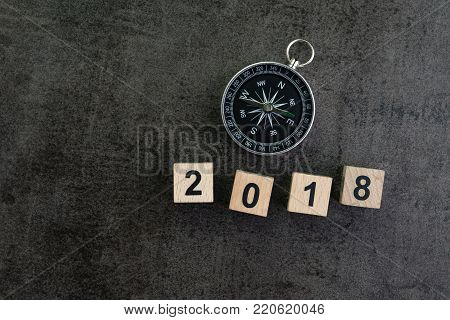 Year 2018 prediction or direction concept with compass and wooden block number 2018 on dark black background.