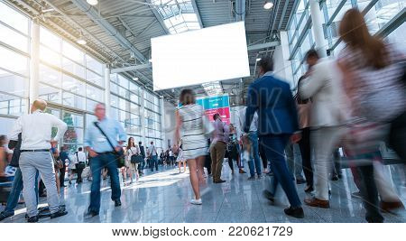 crowd of trade show visitors walking in a hall, including copy space banner. ideal for websites and magazines layouts