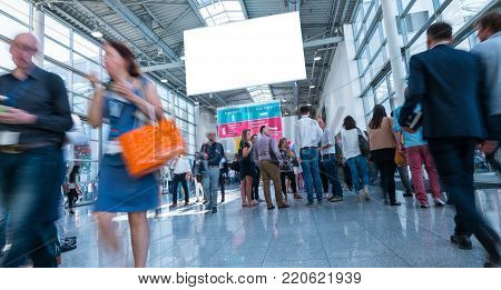 crowd of trade show visitors  rushing in a modern hall, including copy space banner. ideal for websites and magazines layouts