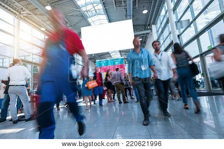 crowd of trade show visitors walking in a modern hall, including copy space banner. ideal for websites and magazines layouts