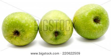 Group of three whole green apples Granny Smith in row isolated on white background
